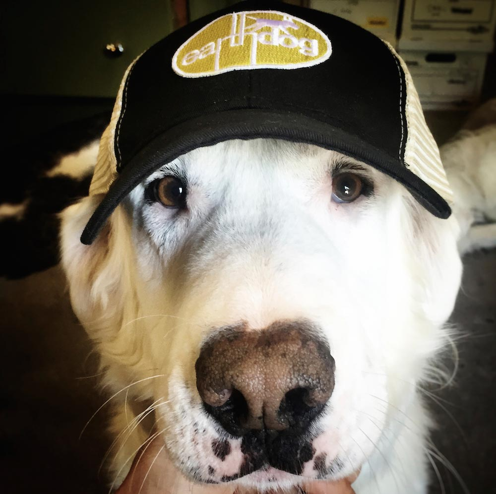 earthdog crew member benny sporting our eco friendly trucker hat