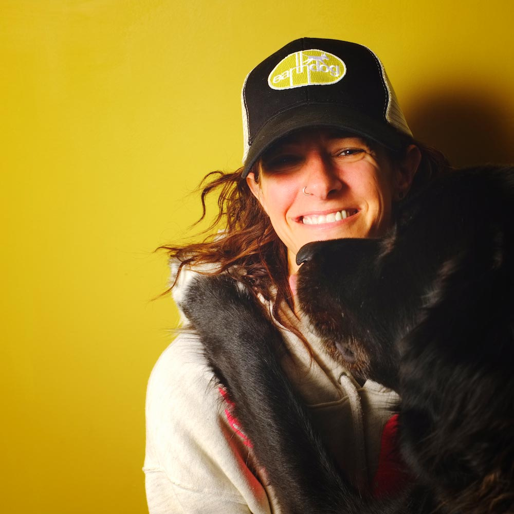 earthdog pack member odin with owner Kym wearing eco friendly trucker hat with embroidered logo patch